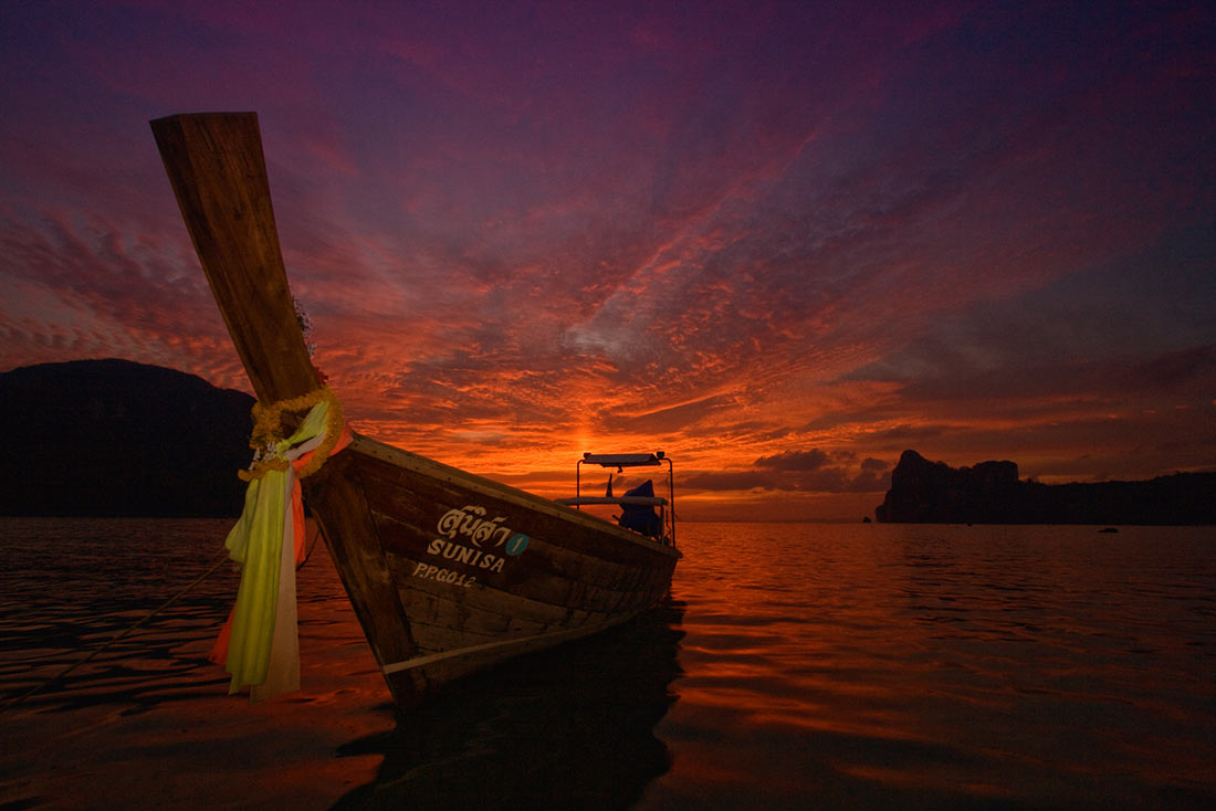 Longtail boat on sunset